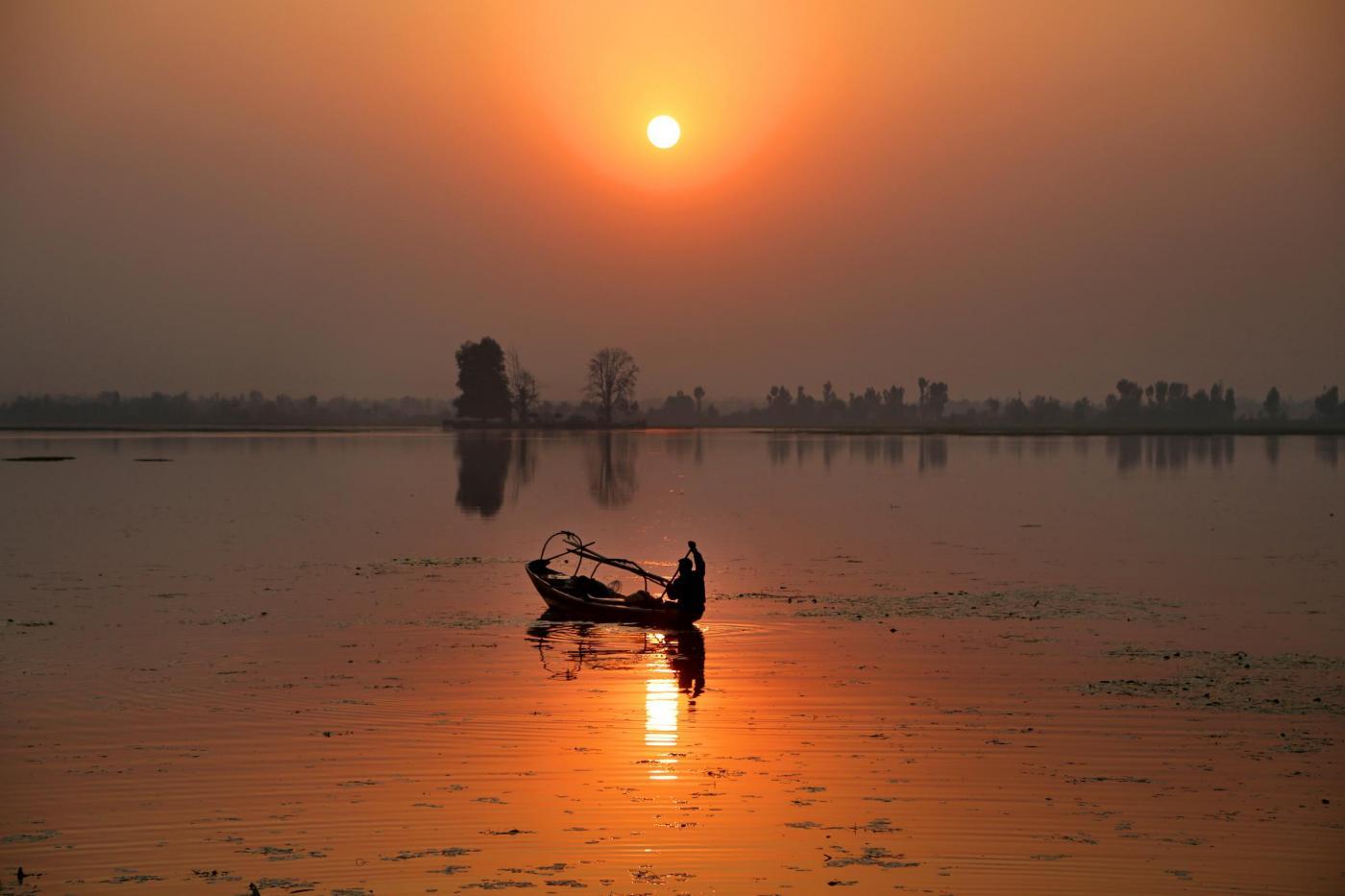 (171030) -- SRINAGAR, Oct. 30, 2017 (Xinhua) -- A fisherman rows his boat in Dal Lake at sunset, in Srinagar, summer capital of Indian-controlled Kashmir, Oct. 30, 2017. (Xinhua/Javed Dar) (lrz)