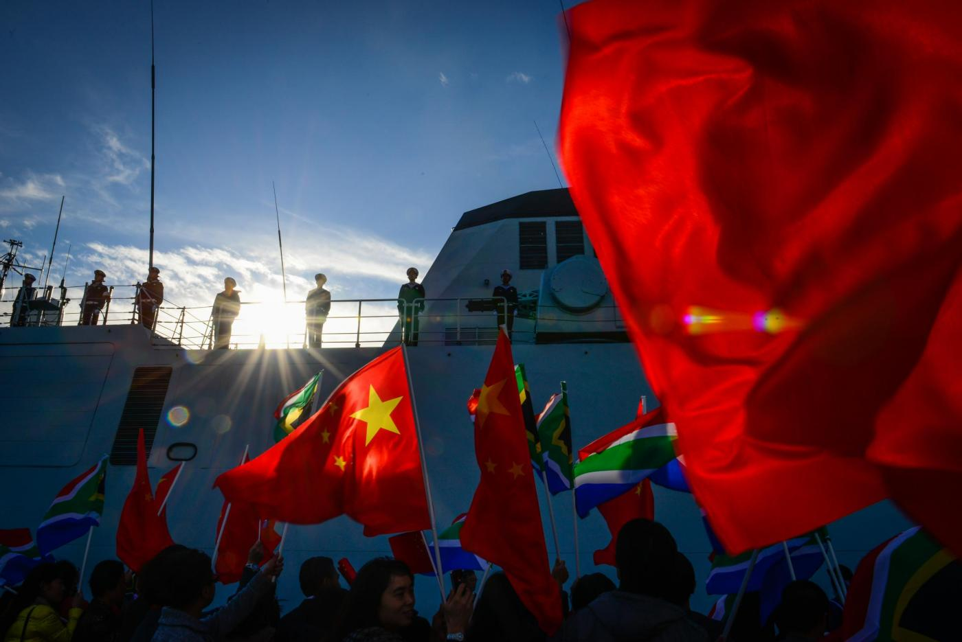 (160516) -- SIMON'S TOWN (SOUTH AFRICA), May 16, 2016 (Xinhua) -- Local Chinese wave flags to welcome the visiting Chinese naval ships at Simon's Town, South Africa, May 16, 2016. The 22nd Chinese naval escort taskforce arrived Monday at the Simon's Town naval base of South Africa for a four-day friendly visit. During the visit, the Chinese navy will conduct friendly exchanges with the South Africa Navy, including mutual visits and open day for public visit. After the port call, the taskforce will conduct joint exercise with the South Africa Navy in South Africa's coastal waters. (Xinhua/Zhai Jianlan)