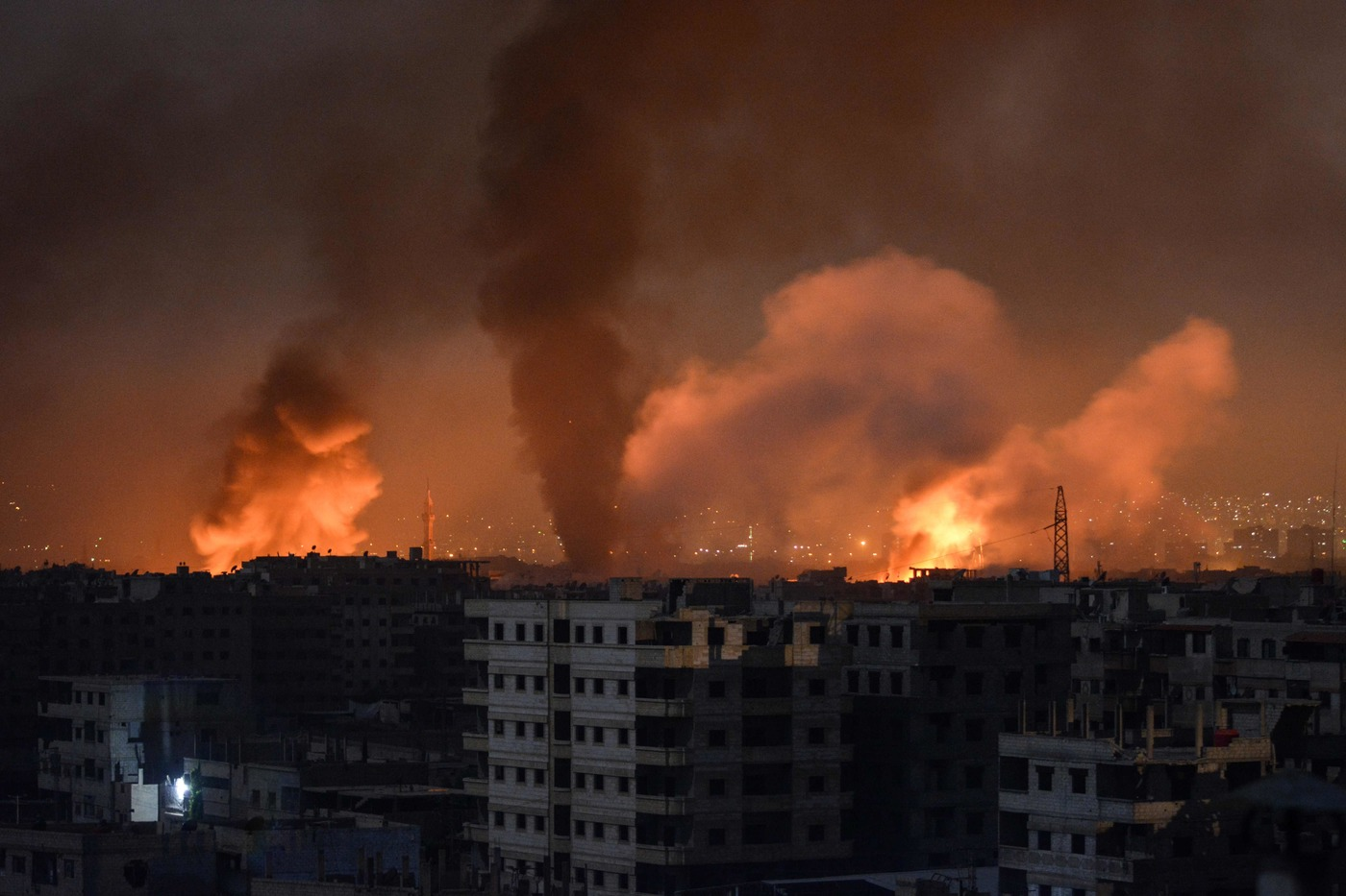 A picture taken late on April 28, 2018 shows smoke plumes rising from explosions in the skyline of a southern district of the Syrian capital Damascus, during regime strikes targeting the Islamic State group in the Palestinian camp of Yarmuk, and neighbouring districts. / AFP PHOTO / Rami al SAYED