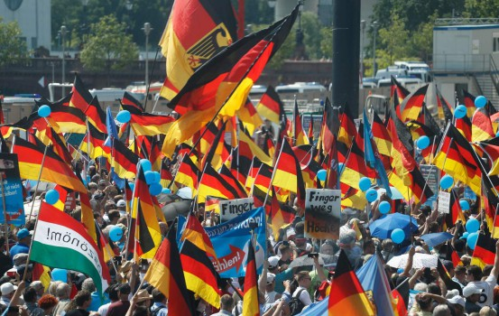 """Alternative for Germany (AfD)'s demonstrators holding placards and German flags gather at the main station in Berlin to attend the """"demonstration for the future of Germany"""" called by the far-right AfD in Berlin on May 27, 2018.  The police estimates 2000 to 2500 people attending the AfD demonstration in front of the main station in Berlin. / AFP PHOTO / Odd ANDERSEN"""