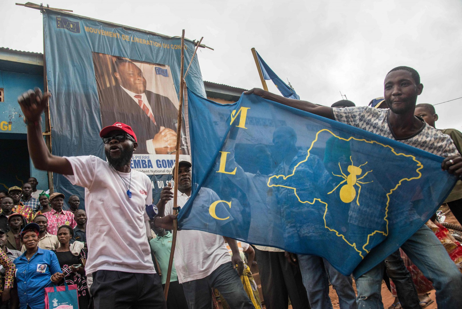 Supporters of former war chief and ex-vice president Jean-Pierre Bemba and his party 'Mouvement de liberation du Congo' (MLC) wait in front of the party's office in Gemena, Democratic Republic of Congo, on July 30, 2018, as he is expected to return to the country after an 11-year absence ahead of December polls. Pierre Bemba, 55, was acquitted in June 2018 of war-crimes charges in The Hague. He has vowed to return to Kinshasa on August 1 to file his election bid. Candidates must physically be in the country to lodge their applications. His party previously said that he would arrive in Gemena, a town in his stronghold of the northwest, on July 31. But on July 30 it said he had not had flight authorisation for landing there. / AFP PHOTO / Junior D. KANNAH