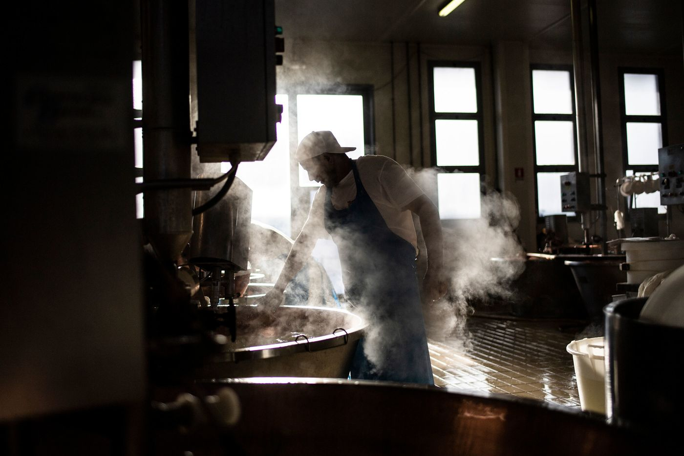Cheesemaker Singh Taljit, a member of the Indian Sikh community, works at a Parmigiano Reggiano factory in the Dall'Aglio Farm on September 1, 2018 in Gattatico, near Reggio Emilia. - Cheesemaker Singh Taljit, who has been doing this job for 16 years makes cheese according to the millennial tradition method.  Italy has a large hidden community of Sikh migrants mostly present in farms in the North of Italy, working as agricultural workers. (Photo by MARCO BERTORELLO / AFP)