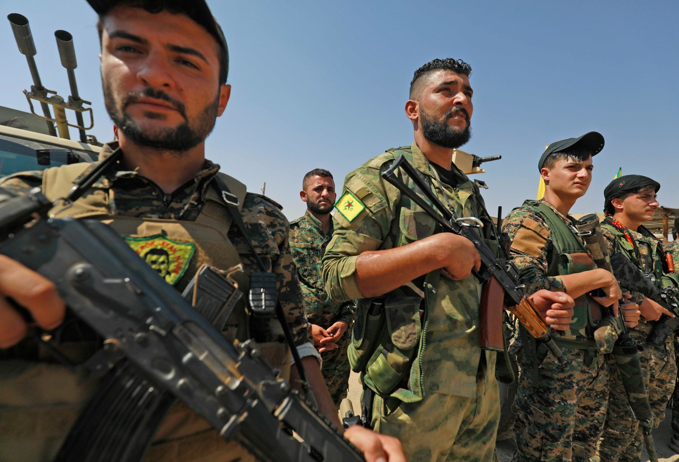 Members of the People's Protection Units (YPG), part of the of the Syrian Democratic Forces (SDF), gather in the town of Shadadi, about 60 kilometres (37 miles) south of the northeastern Syrian city of Hassakeh, on September 11, 2018. - The US-backed SDF, an alliance of Kurdish and Arab fighters, launched on September 10 an assault against a dwindling pocket of territory held by the Islamic State group in the town of Hajin in eastern Syria near the border with Iraq. (Photo by Delil SOULEIMAN / AFP)