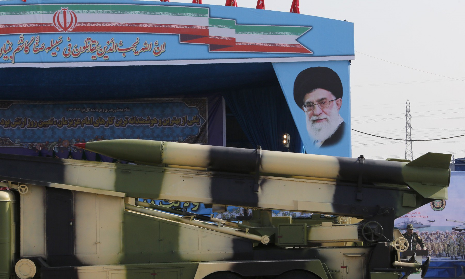 "An Iranian military truck carries missiles past a portrait of Iran's Supreme Leader Ayatollah Ali Khamenei during a parade on the occasion of the country's annual army day on April 18, 2018 in Tehran. President Hassan Rouhani said during the parade that Iran ""does not intend any aggression"" against its neighbours but will continue to produce all the weapons it needs for its defence. / AFP PHOTO / ATTA KENARE"