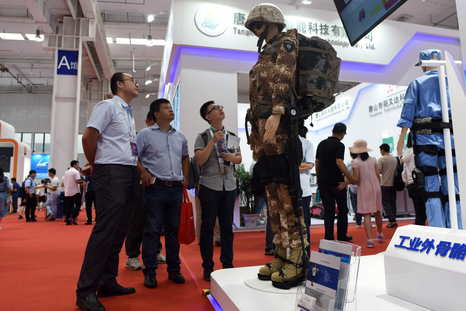 A group of men look at a exoskeleton robot at the 2018 World Robot Conference in Beijing on August 15, 2018. (Photo by WANG Zhao / AFP)