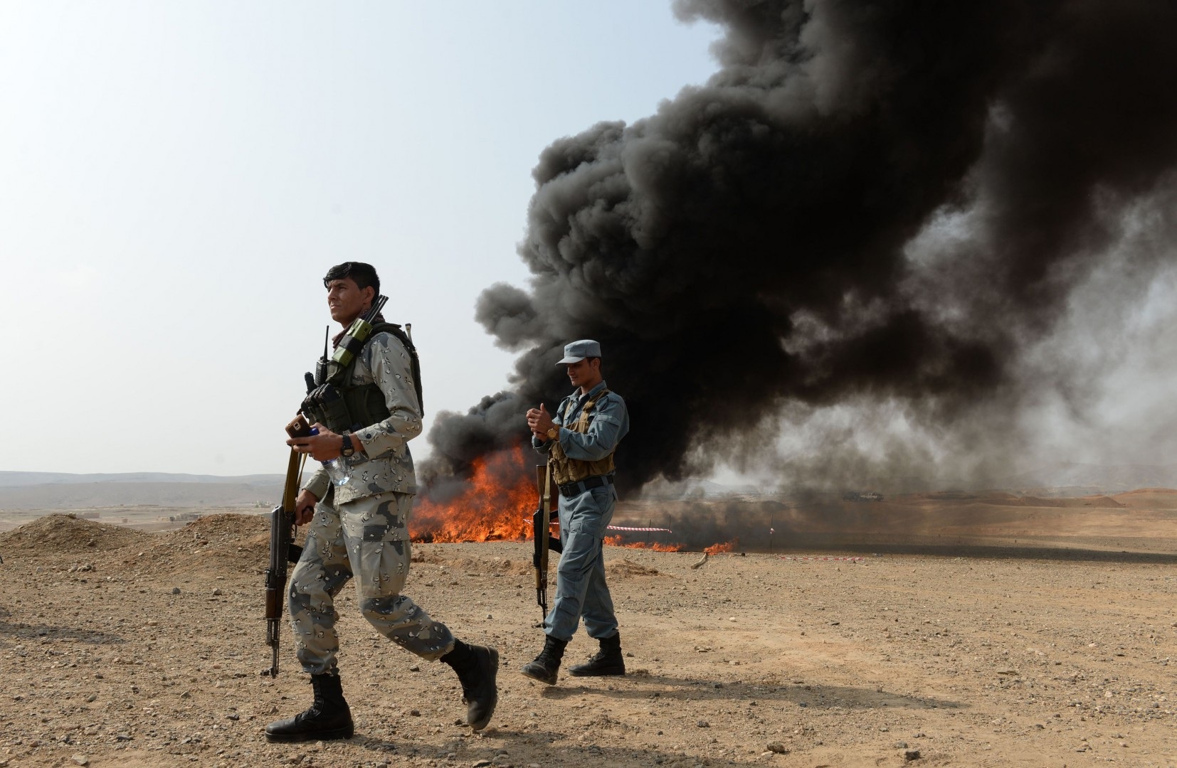 Afghan security forces walk near a pile of burning drugs and alcohol on the outskirts of Jalalabad on September 24, 2018. - Afghan authorities burned around 20 tons of narcotics which were seized during operations in Nangarhar province, officials said. (Photo by NOORULLAH SHIRZADA / AFP)