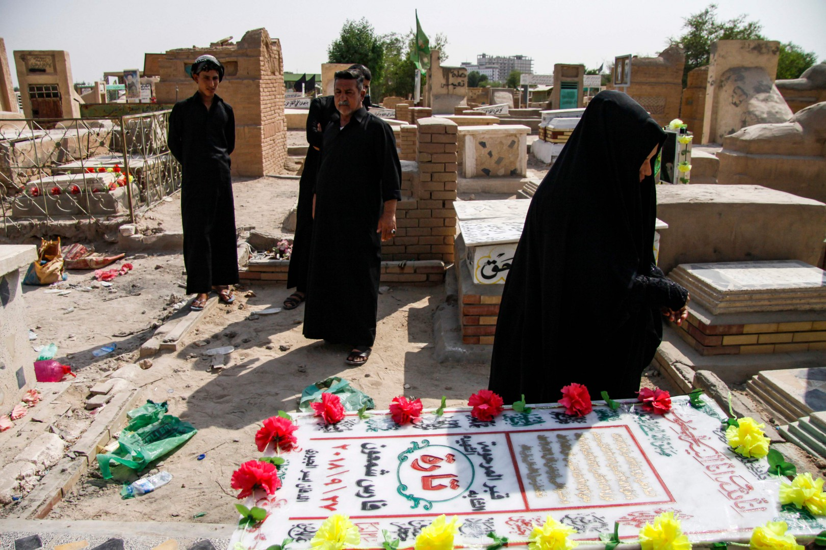 """An Iraqi woman is seen around the grave of slain model and Instagram starlet Tara Fares in the central holy shrine city of Najaf on October 2, 2018. - Fares was shot dead at the wheel of her Porsche convertible in central Baghdad on September 27, sending ripples through social media circles. The interior ministry opened a probe into yesterday's murder of the 22-year-old who suffered """"three fatal bullet wounds"""" as she drove through the capital's Camp Sarah district. (Photo by Haidar HAMDANI / AFP)"""