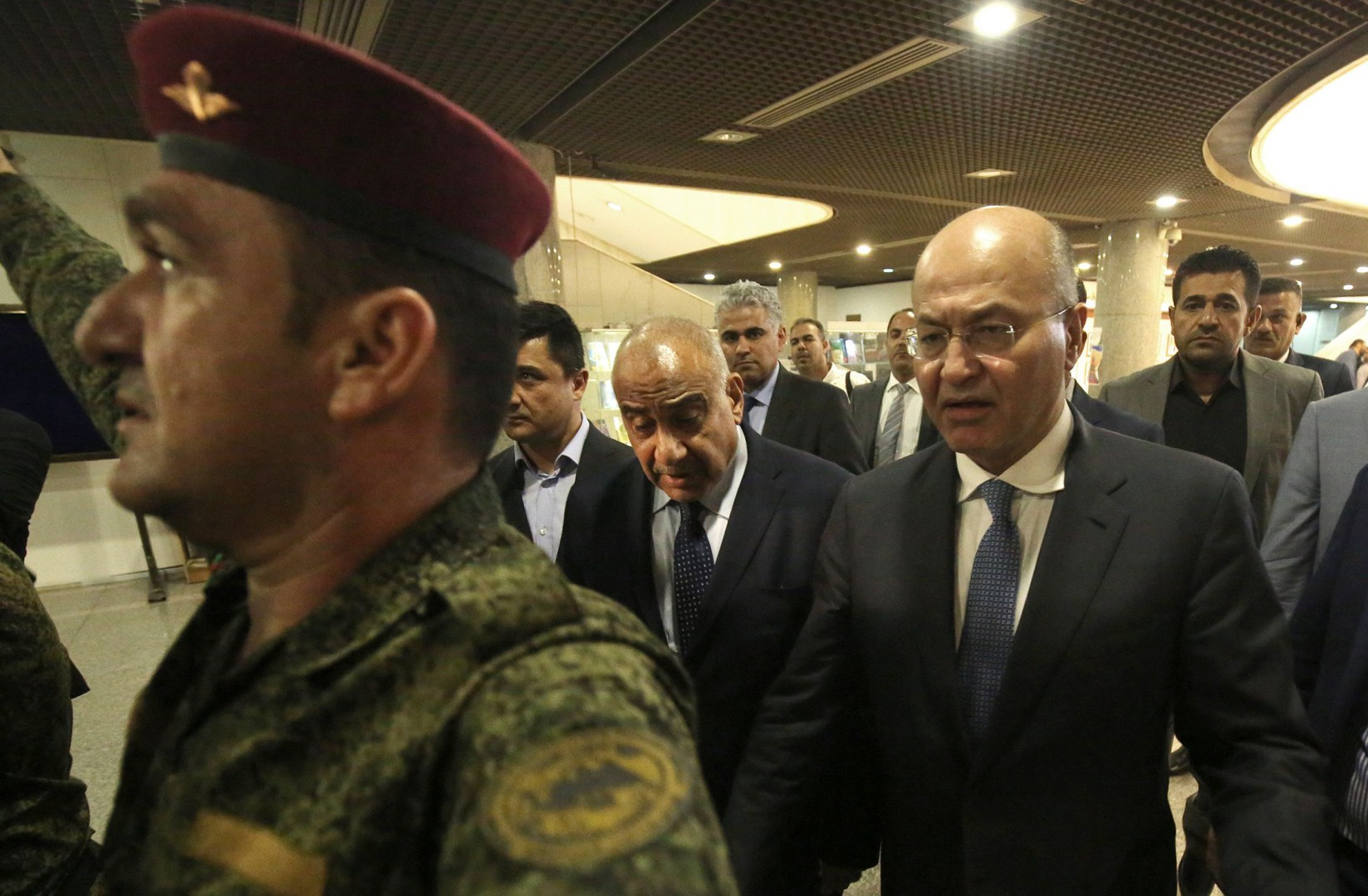 Newly designated Iraqi Prime Minister Adel Abdul Mahdi (C L) walks out of the Parliament with newly-elected Iraqi President Barham Saleh (C R)in Baghdad on October 2, 2018. (Photo by AHMAD AL-RUBAYE / AFP)