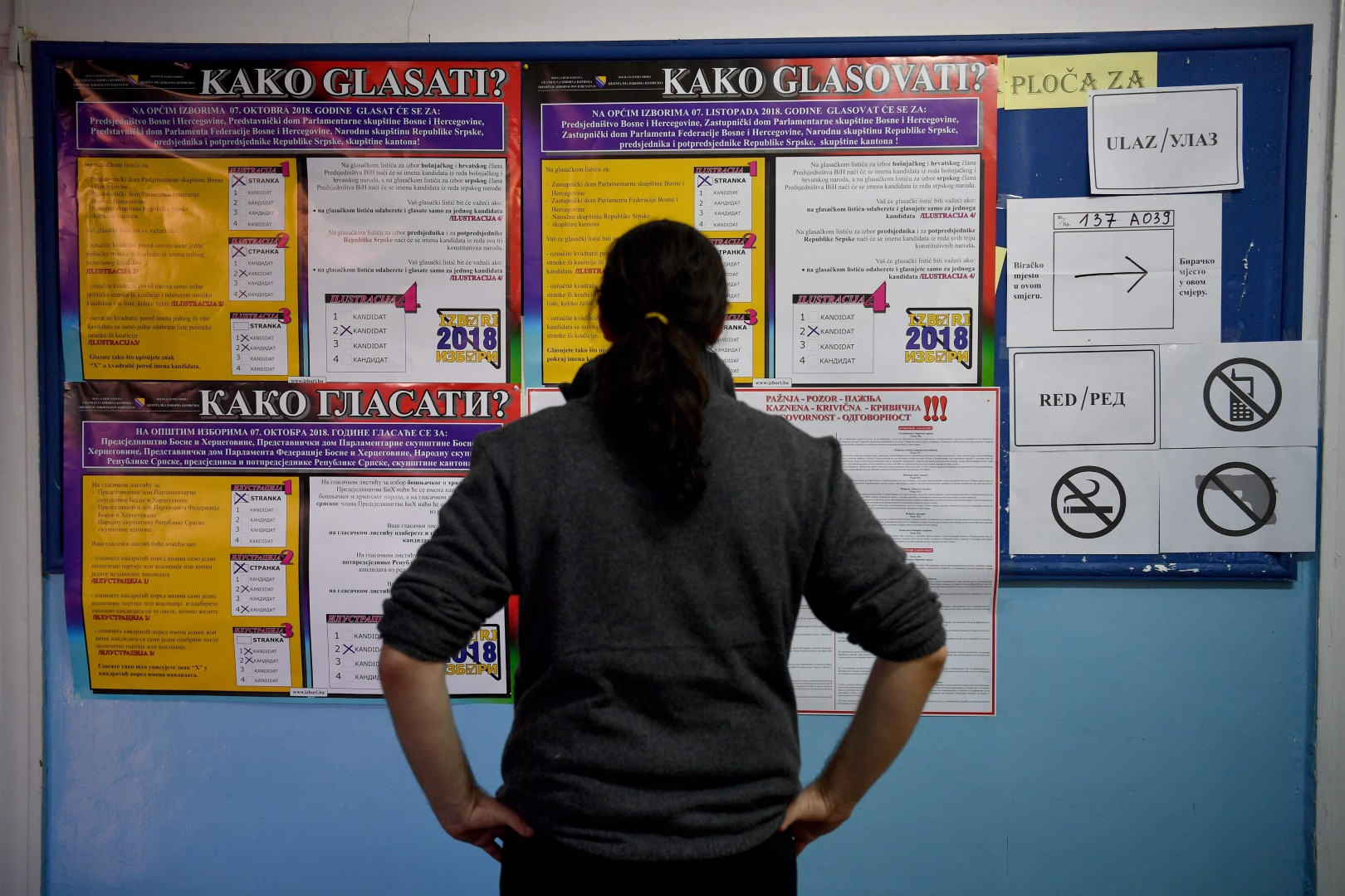 TOPSHOT - A Bosnian looks at the instructions on how to cast a ballot at a polling station in Sarajevo on October 7, 2018. - Bosnians headed to the polls to elect leaders who will steer the future of a poor nation shackled by the communal divides that fuelled its brutal war more than two decades ago. While the list of woes facing the country is long, many Bosnians say they have lost faith in a corrupt political class that clings to power by inflaming nationalism that threatens to pull the country apart. (Photo by ANDREJ ISAKOVIC / AFP)