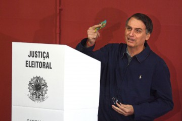 Brazil's right-wing presidential candidate for the Social Liberal Party (PSL) Jair Bolsonaro shows his vote during general elections, in Rio de Janeiro, Brazil, on October 7, 2018. - Polling stations opened in Brazil on Sunday for the most divisive presidential election in the country in years, with far-right lawmaker Jair Bolsonaro the clear favorite in the first round. About 147 million voters are eligible to cast ballots and choose who will rule the world's eighth biggest economy. New federal and state legislatures will also be elected. (Photo by Mauro PIMENTEL / AFP)