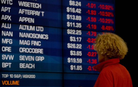 A visitor to the Australian Securities Exchange (ASX) looks at share prices on a big screen in Sydney on October 11, 2018. - The Australian share market joined the regional bloodbath after the sell off on Wall Street, plunging to a more than five-month low as all sectors dropped into the red. (Photo by PETER PARKS / AFP)