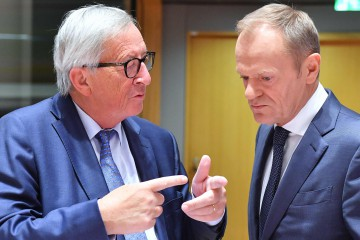 European Commission President Jean-Claude Juncker (L) and European Council President Donald Tusk greet each others at the start of a tripartite social summit at the European Council in Brussels on October 16, 2018. (Photo by Emmanuel DUNAND / AFP)