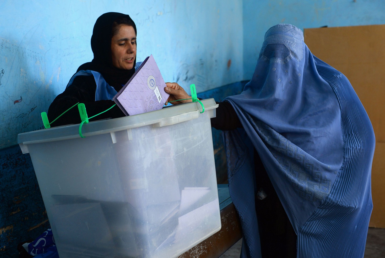 An Afghan voter casts her ballot at a polling centre for the country's legislative election in Herat on October 20, 2018. - Multiple explosions rocked polling centres across Kabul on October 20, causing dozens of casualties, amid growing anger among voters as they waited hours to cast their ballots in long-delayed legislative elections. (Photo by HOSHANG HASHIMI / AFP)