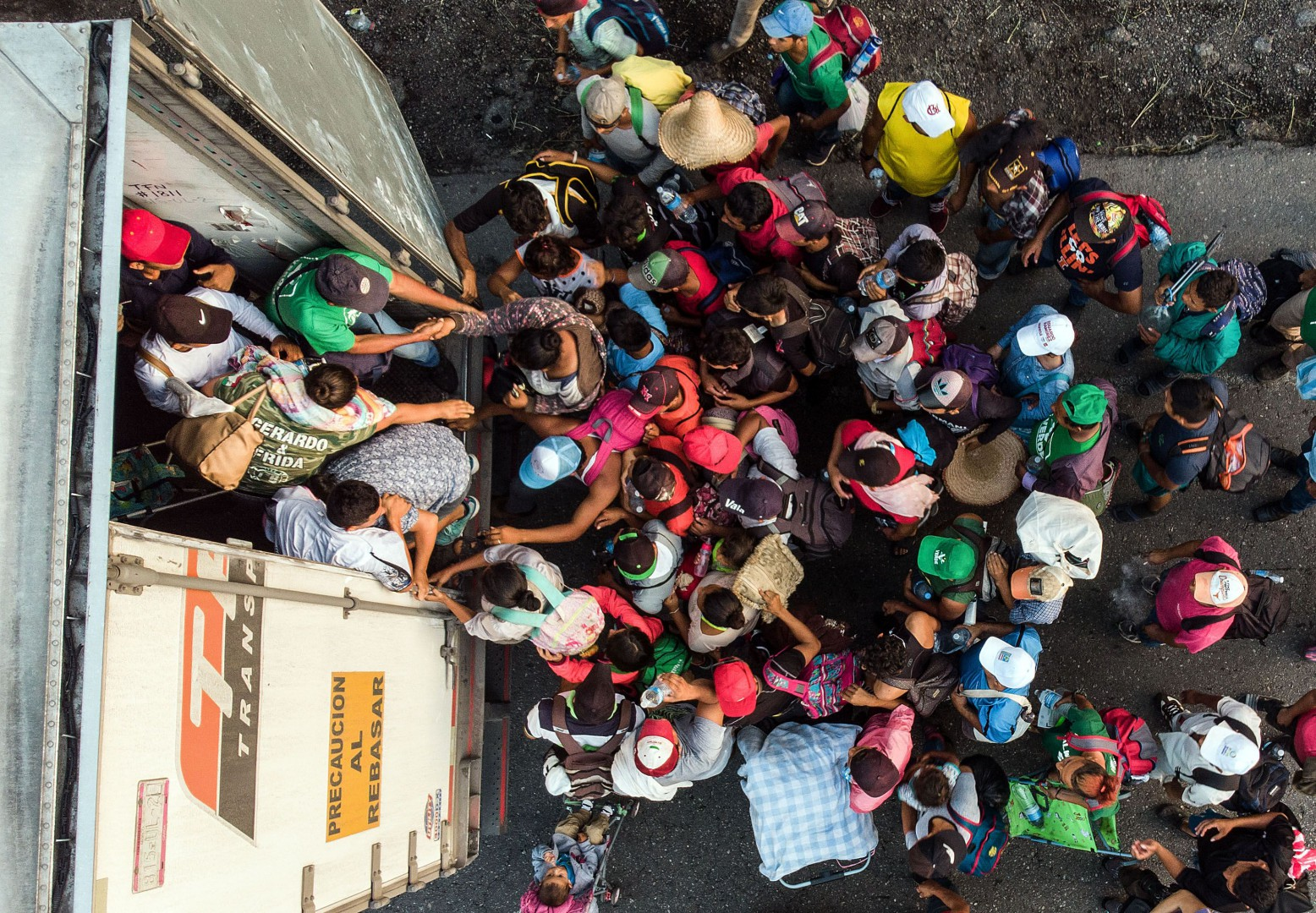 "TOPSHOT - Honduran migrants taking part in a caravan heading to the US, get on a truck, near Pijijiapan, southern Mexico on October 26, 2018. - The Pentagon is expected to deploy about 800 troops to the US-Mexico border, two US officials told AFP on Thursday, after President Donald Trump said the military would help tackle a ""national emergency"" and called on a caravan of US-bound migrants to turn around. (Photo by Guillermo Arias / AFP)"