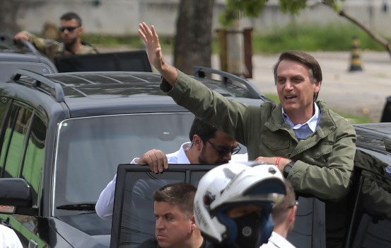 Jair Bolsonaro, far-right lawmaker and presidential candidate for the Social Liberal Party (PSL), waves to supporters during the second round of the presidential elections, in Rio de Janeiro, Brazil on October 28, 2018. - Brazilians will choose their president today during the second round of the national elections between the far-right firebrand Jair Bolsonaro and leftist Fernando Haddad (Photo by Carl DE SOUZA / AFP)