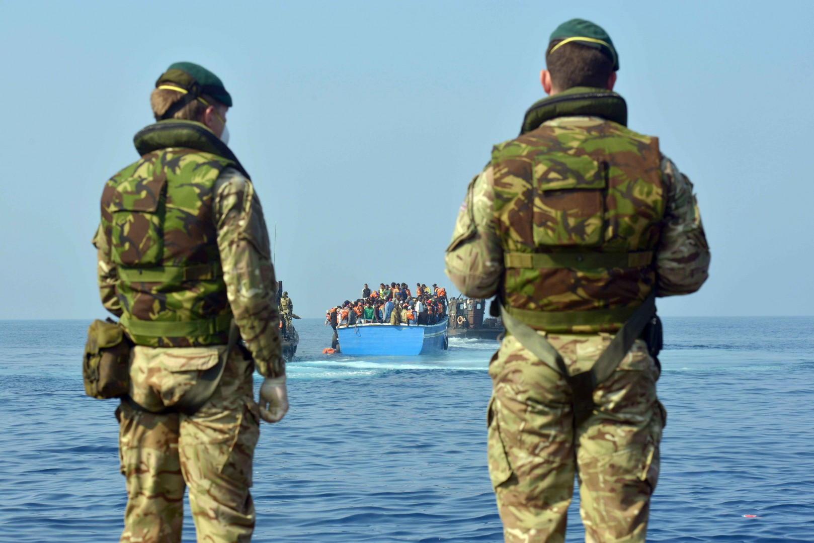 """Royal Marines from HMS Bulwark help rescue migrants stranded on a boat, thirty miles off the Libyan coast.  PRESS ASSOCIATION Photo. Picture date: Sunday June 7, 2015. The rescued migrants were taken to the Royal Navy ship where they were searched and processed before being handed over to the Italian authorities. Britain is a country that """"doesn't walk on by"""", David Cameron said as HMS Bulwark undertook another rescue mission off Libya. The Royal Navy warship picked up at least 500 migrants found in four boats in the seas off the north African country. Arriving at the G7 summit in Garmisch-Partenkirchen, Germany, the Prime Minister said the flagship had been deployed because the UK is a """"country with a conscience"""".  But he warned that the causes of the mass exodus from Libya must be dealt with, not just the consequences. See PA story DEFENCE Migrants. Photo credit should read: Rowan Griffiths/Daily Mirror/PA Wire"""