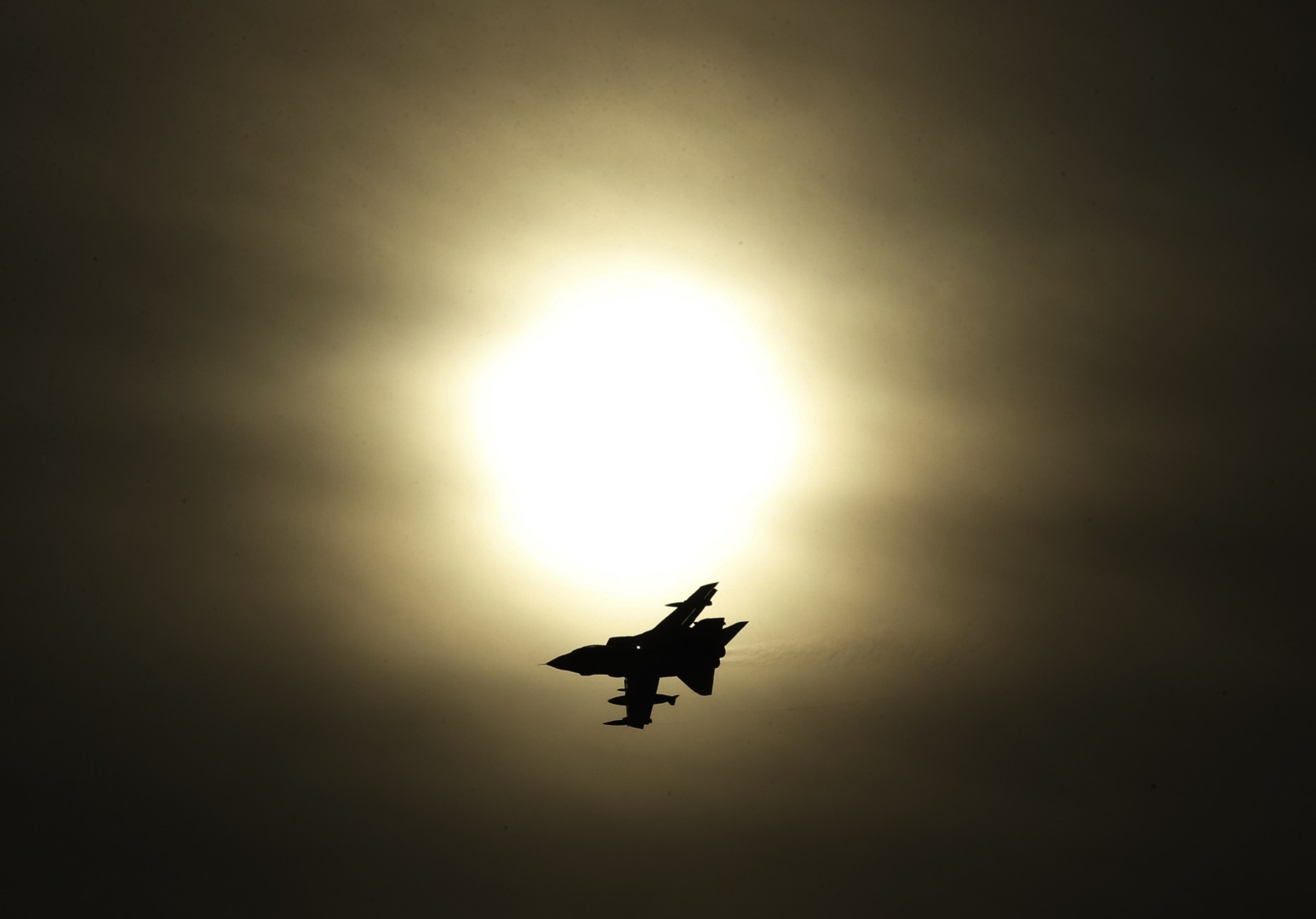 A Tornado jet flying past the sun after taking off from RAF Lossiemouth in Scotland, as RAF Tornado jets carried out the first British bombing runs over Syria, the Ministry of Defence has confirmed. Picture date: Thursday December 3, 2015. The air strikes were carried out within hours of a vote by MPs in the Commons to back extending operations against Islamic State (IS) from neighbouring Iraq. See PA story POLITICS Syria. Photo credit should read: Danny Lawson/PA Wire