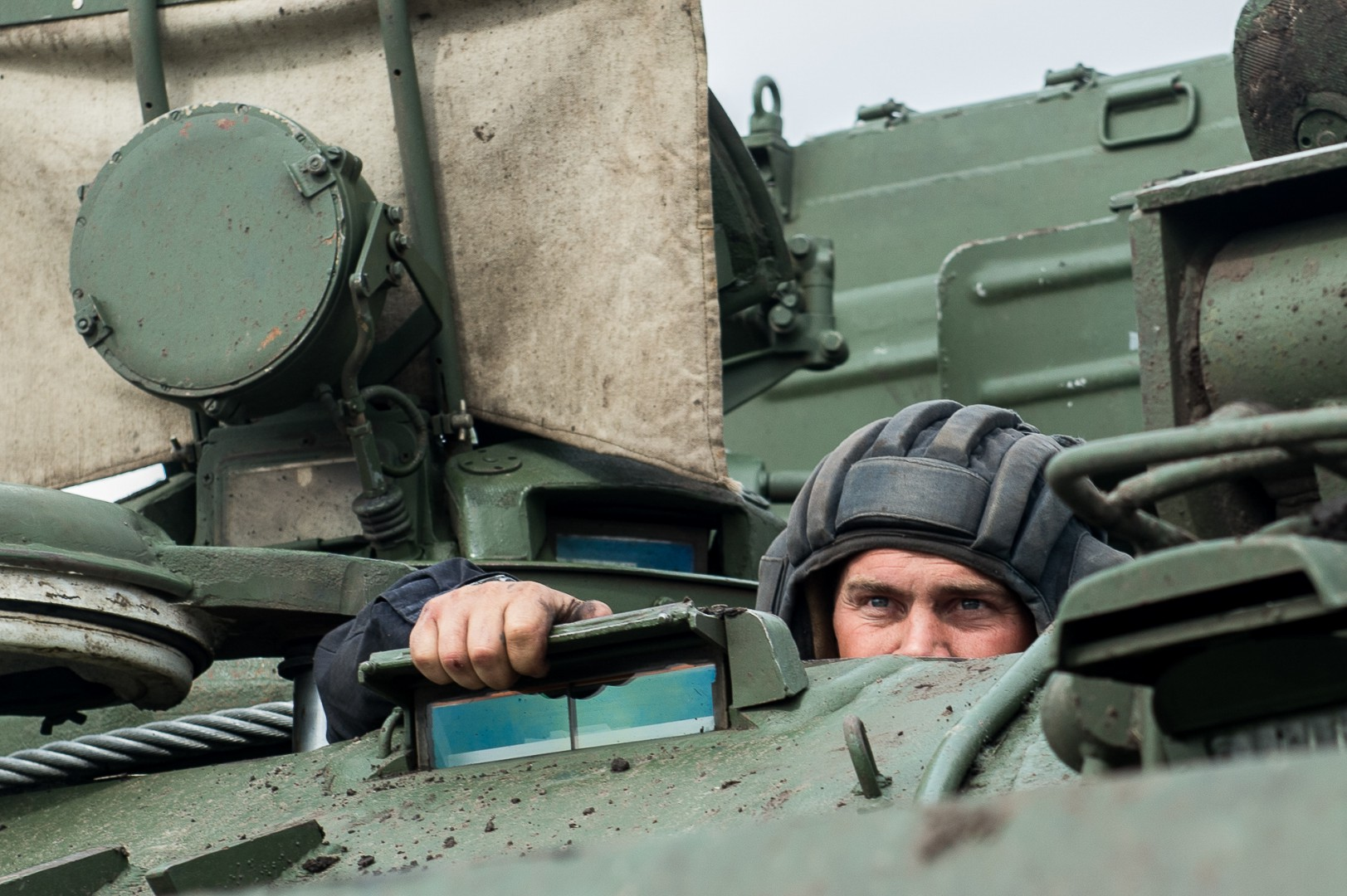 "Russian tank crew member looks out of the tank during the ""Maintenance battalion"" contest in Omsk region, Russia, on Aug. 9, 2017. (Xinhua/Evgeny Sinitsyn)"