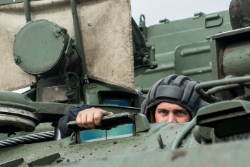 """Russian tank crew member looks out of the tank during the """"Maintenance battalion"""" contest in Omsk region, Russia, on Aug. 9, 2017. (Xinhua/Evgeny Sinitsyn)"""