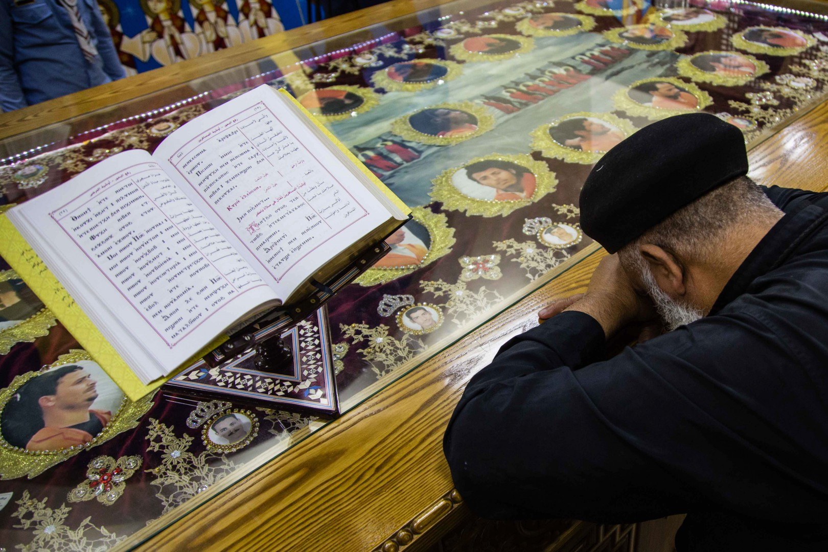 A priest mourns over the portraits of 20 Egyptian Coptic Christian men who were beheaded by jihadists on the beach of Sirte in Libya in 2015, during their funereal ceremony in the Martyrs Church in the village of Al-Our in Egypt's southern province of Minya on May 15, 2018, after their bodies were repatriated to Egypt.  / AFP PHOTO / IBRAHIM EZZAT
