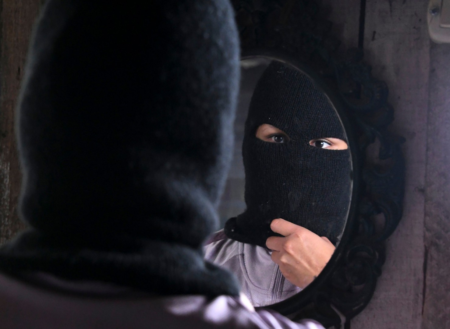 A person wearing a balaclava offers an interview to AFP in the poor neighbourhood of Nueva Capital, on the outskirts of Tegucigalpa, on May 13, 2018. Missionaries from the United States who met three Honduran ex-members of the Mara Salvatrucha (MS-13) gang, told AFP that they wanted to hear about the causes of migration to the US because they are critical of President Donald Trump's anti-immigrant policies. According to the ex-gang members, who aspired to a better world, no one is in a gang because they want to but for necessity and that young people emigrate because of family disintegration, lack of employment, deficient health and education services and, in some cases, fleeing from gang recruitments. / AFP PHOTO / Orlando SIERRA