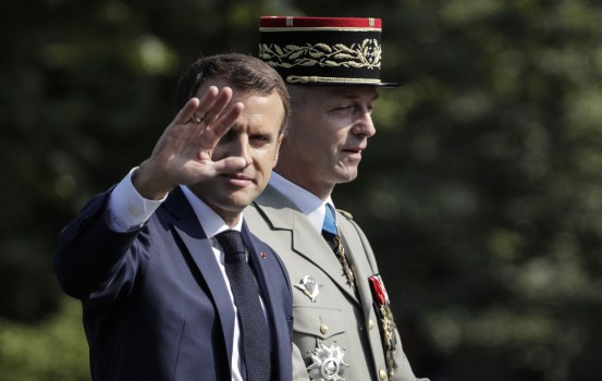 French President Emmanuel Macron (L) and Chief of the Defence Staff of the French Army General Francois Lecointre (R) take part in the annual Bastille Day military parade on the Champs-Elysees avenue in Paris on July 14, 2018.  / AFP PHOTO / Thomas SAMSON