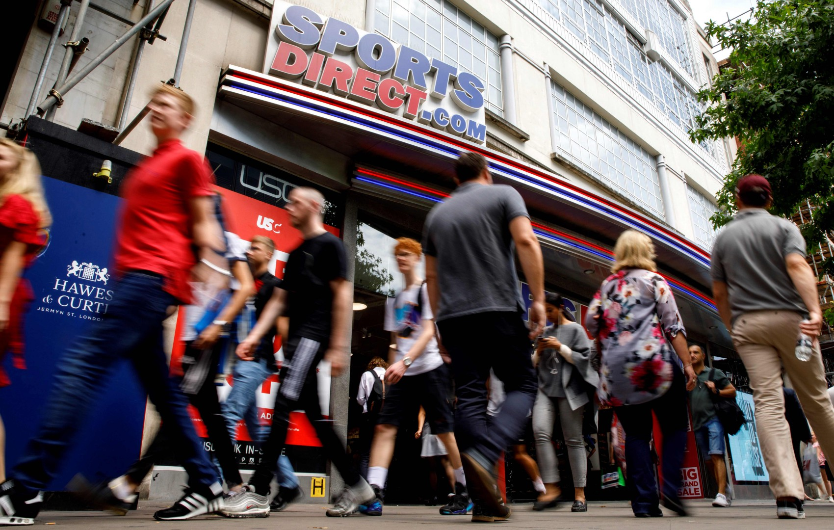 Shoppers walk past a Sports Direct shop on Oxford Street in central London on July 19, 2018. Sports Direct Thursday reported a 72.5 percent drop in pre-tax profits to £77.5 million for the year ending  April 29, 2018, down from £281.6 million the previous year. / AFP PHOTO / Tolga AKMEN