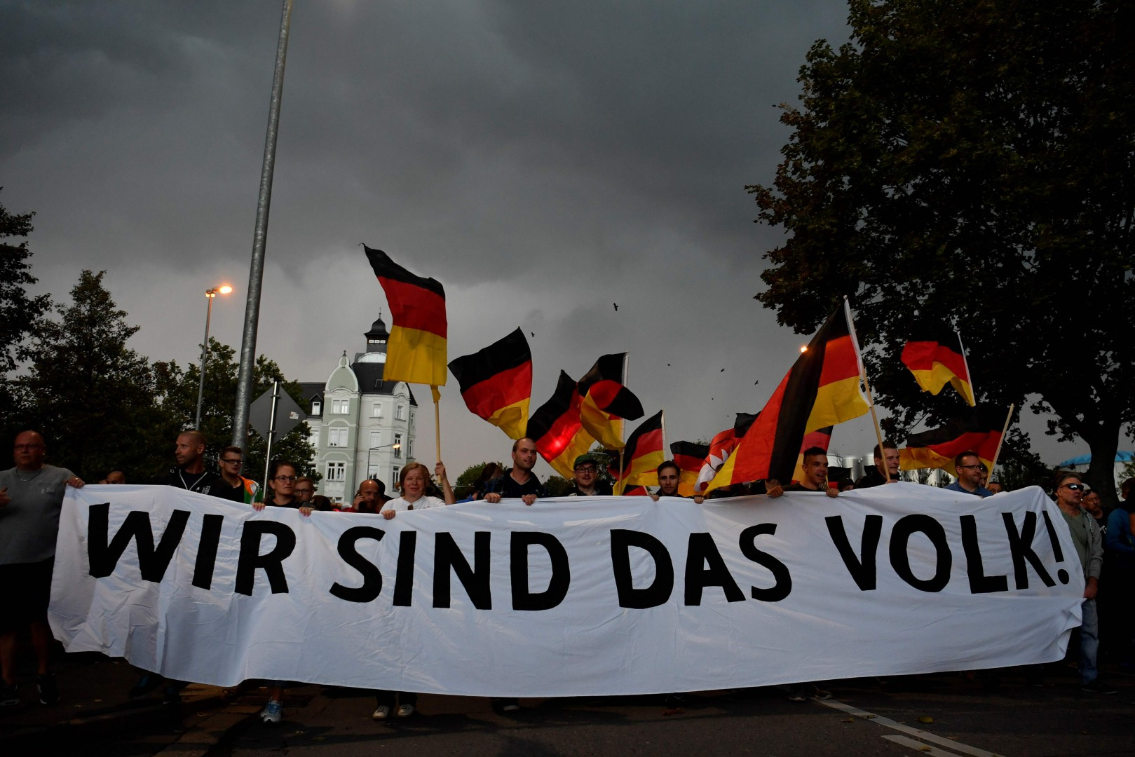 """TOPSHOT - CORRECTION - People hold a giant banner reading """"we are the people"""" during a march organised by the right-wing populist """"Pro Chemnitz"""" movement, on September 7, 2018 in Chemnitz, the flashpoint eastern city that saw protests marred by neo-Nazi violence. - The rally is to be followed by a concert which counterprotesters called """"Stronger Together"""" urging """"openness and diversity"""". (Photo by John MACDOUGALL / AFP) / ìThe erroneous mention[s] appearing in the metadata of this photo by John MACDOUGALL has been modified in AFP systems in the following manner: [a march organised by the Pro Chemnitz movement] instead of [organised by Pro Chemnitz movement, Pedida and AfD]. Please immediately remove the erroneous mention[s] from all your online services and delete it (them) from your servers. If you have been authorized by AFP to distribute it (them) to third parties, please ensure that the same actions are carried out by them. Failure to promptly comply with these instructions will entail liability on your part for any continued or post notification usage. Therefore we thank you very much for all your attention and prompt action. We are sorry for the inconvenience this notification may cause and remain at your disposal for any further information you may require.î"""