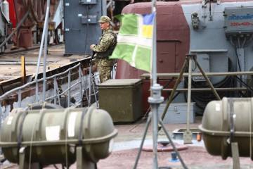 Ukrainian frontier soldier stands aboard a patrol boat at the commercial port of Mariupol on the Sea of Azov on August 14, 2018. - The small sea is located in a zone of heightened tensions between Russia and Ukraine: bordering the Crimean peninsula annexed by Russia and the Kremlin-backed rebel regions of eastern Ukraine. (Photo by Aleksey FILIPPOV / AFP)