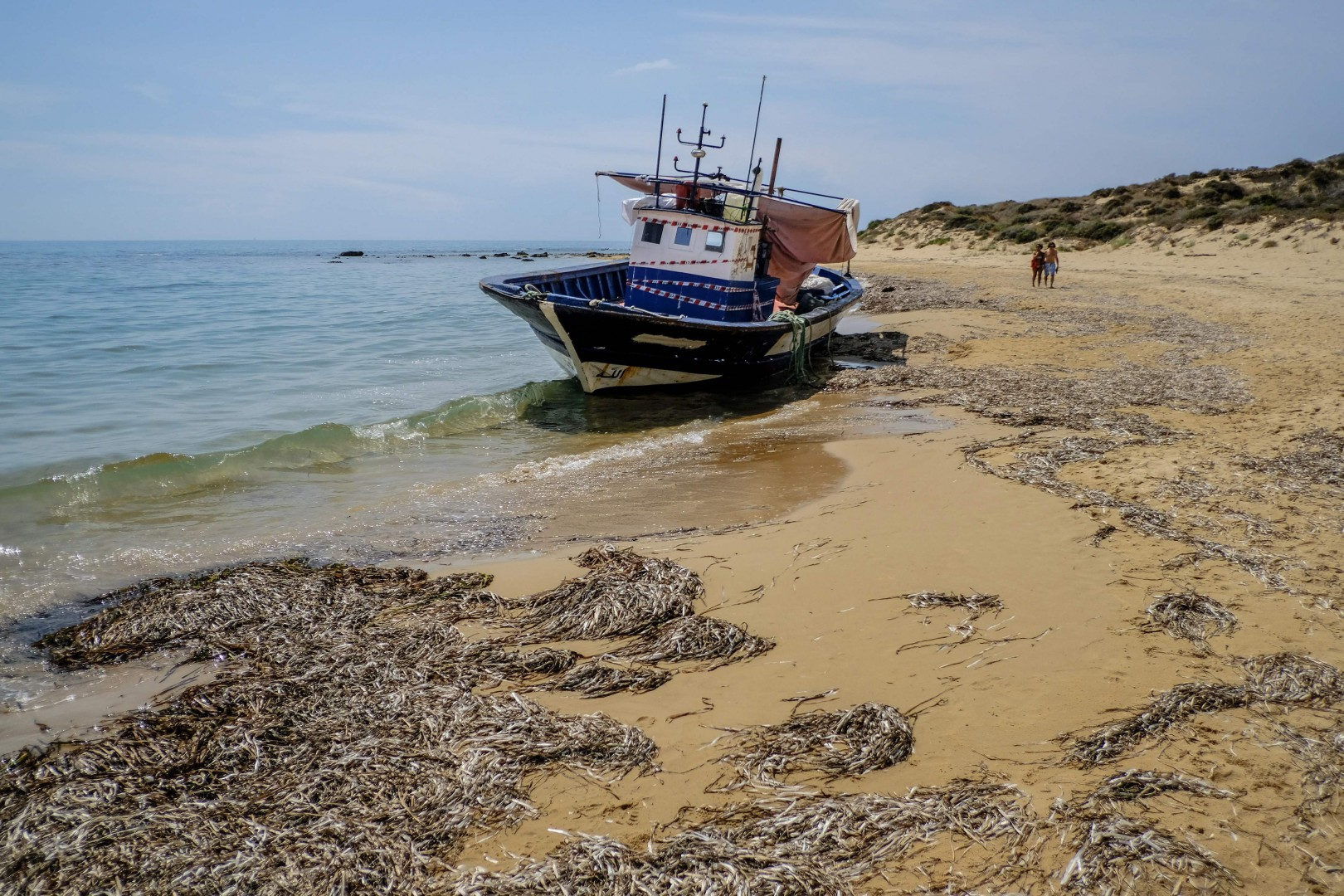 This picture taken on August 21, 2018 shows a boat used by migrants, with the seals of seizure by the Italian carabinieri, stranded on the beach of Capo Bianco, near Ribera municipality, in the province of Agrigento. (Photo by Andreas SOLARO / AFP)