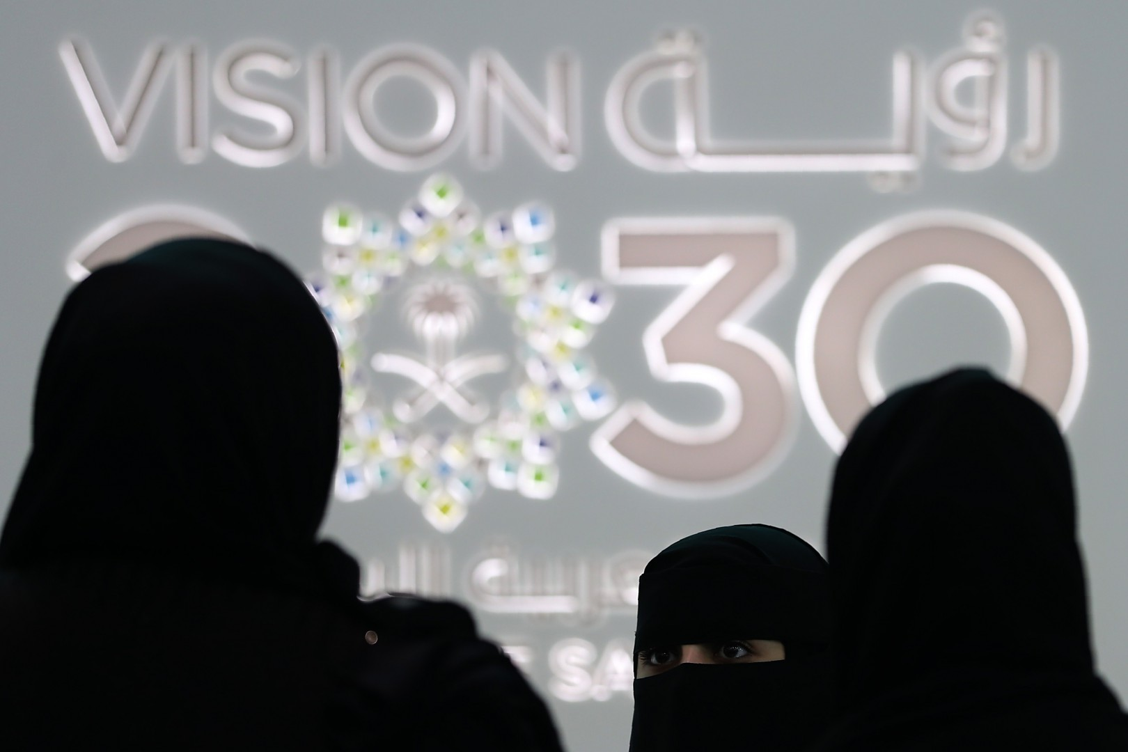 """Saudi women stand next to the Saudi pavilion (vision 2030) at the Gitex 2018 exhibition at the Dubai World Trade Center in Dubai on October 16, 2018. - Gitex (""""Gulf Information Technology Exhibition"""") is a consumer computer and electronics trade show. (Photo by KARIM SAHIB / AFP)"""