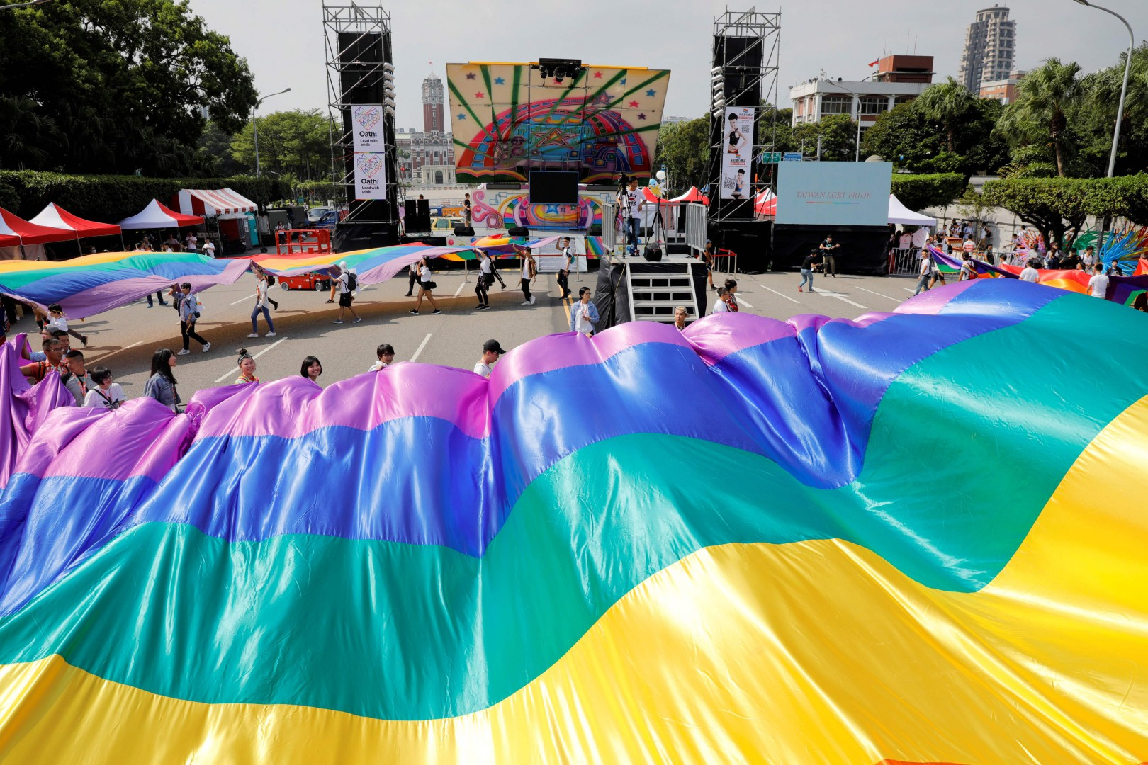Participants rehearse with a large rainbow banner before the start of a gay pride parade in Taipei on October 27, 2018. - Thousands were gathered at Taipei's Gay Pride parade on October 27 -- the biggest in Asia -- ahead of a landmark vote next month on LGBT rights on the island. (Photo by Daniel Shih / AFP)