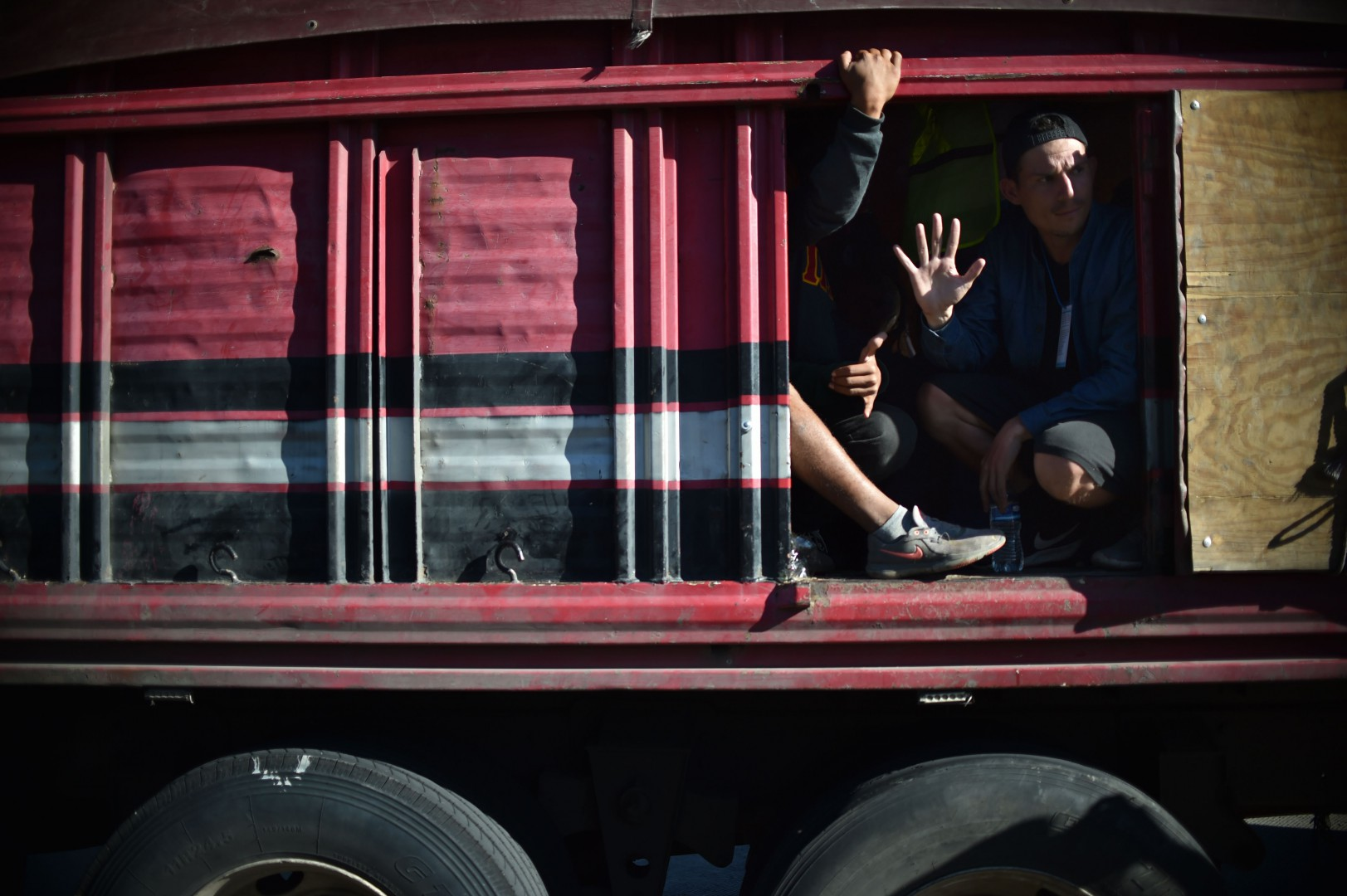 Migrants from poor Central American countries -mostly Hondurans- moving towards the United States in hopes of a better life or to escape violence take a ride on the back of a truck along the Mexico City-Puebla highway in San Marcos, Mexico, on November 5, 2018. - US President Donald Trump has ordered regular army troops to the US-Mexican border as a caravan of a few thousand impoverished migrants slowly marches toward the boundary. (Photo by Rodrigo ARANGUA / AFP)