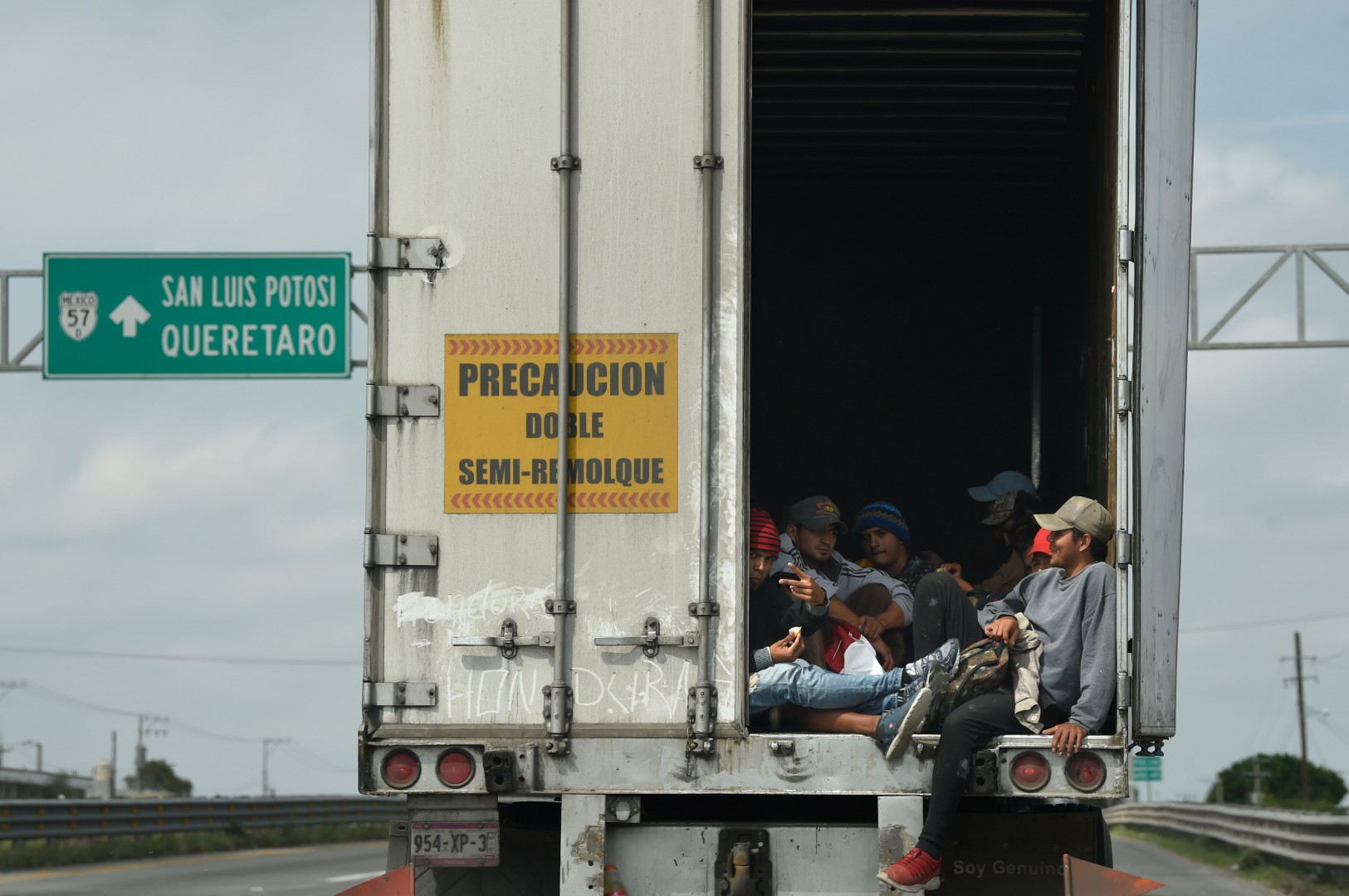 Migrants from poor Central American countries -mostly Hondurans- moving towards the United States in hopes of a better life or to escape violence, get a ride on the bed of a truck as they head to Queretaro after leaving the Mexican capital to continue their trek north, on November 10, 2018. - The United States embarked Friday on a policy of automatically rejecting asylum claims of people who cross the Mexican border illegally in a bid to deter Central American migrants and force Mexico to handle them. (Photo by Alfredo ESTRELLA / AFP)
