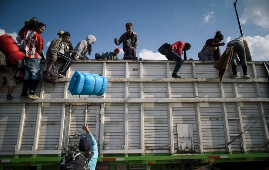 TOPSHOT - Central American migrants -mostly Hondurans- taking part in a caravan heading to the US, descend from a truck, on arrival at a temporary shelter in Irapuato, Guanajuato state, Mexico on November 11, 2018. - The trek from tropical Central America to the huge capital of Mexico is declining the health of the migrant caravan that endures extreme climate changes, as well as overcrowding and physical exhaustion, and still has to face the desert that leads to the United States. (Photo by ALFREDO ESTRELLA / AFP)