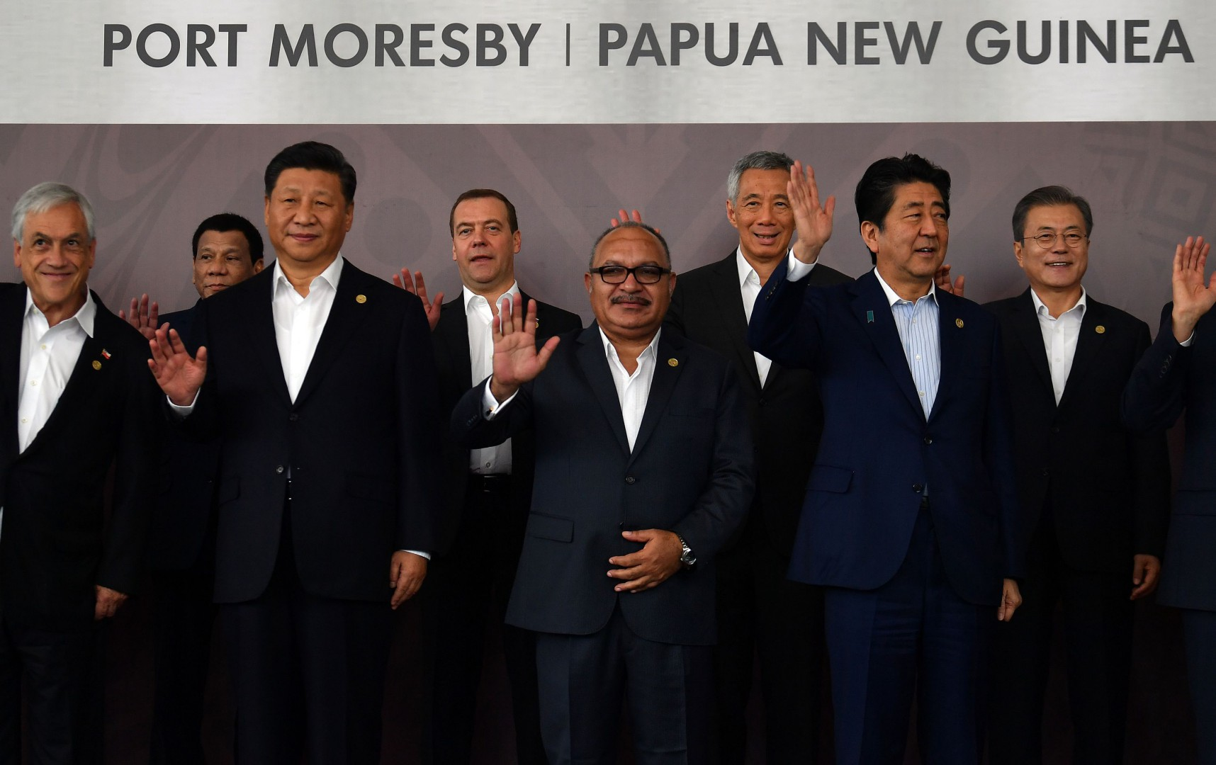 "(L to R-front row) Chile's President Sebastian Pinera, China's President Xi Jinping, Papua New Guinea's Prime Minister Peter O'Neill and Japan's Prime Minister Shinzo Abe wave with (back row L to R) Philippine President Rodrigo Duterte, Russia's Prime Minister Dmitry Medvedev, Singapore's Prime Minister Lee Hsien Loong and South Korea's President Moon Jae-in as they pose for a ""family photo"" during the Asia-Pacific Economic Cooperation (APEC) Summit in Port Moresby on November 18, 2018. (Photo by SAEED KHAN / AFP)"