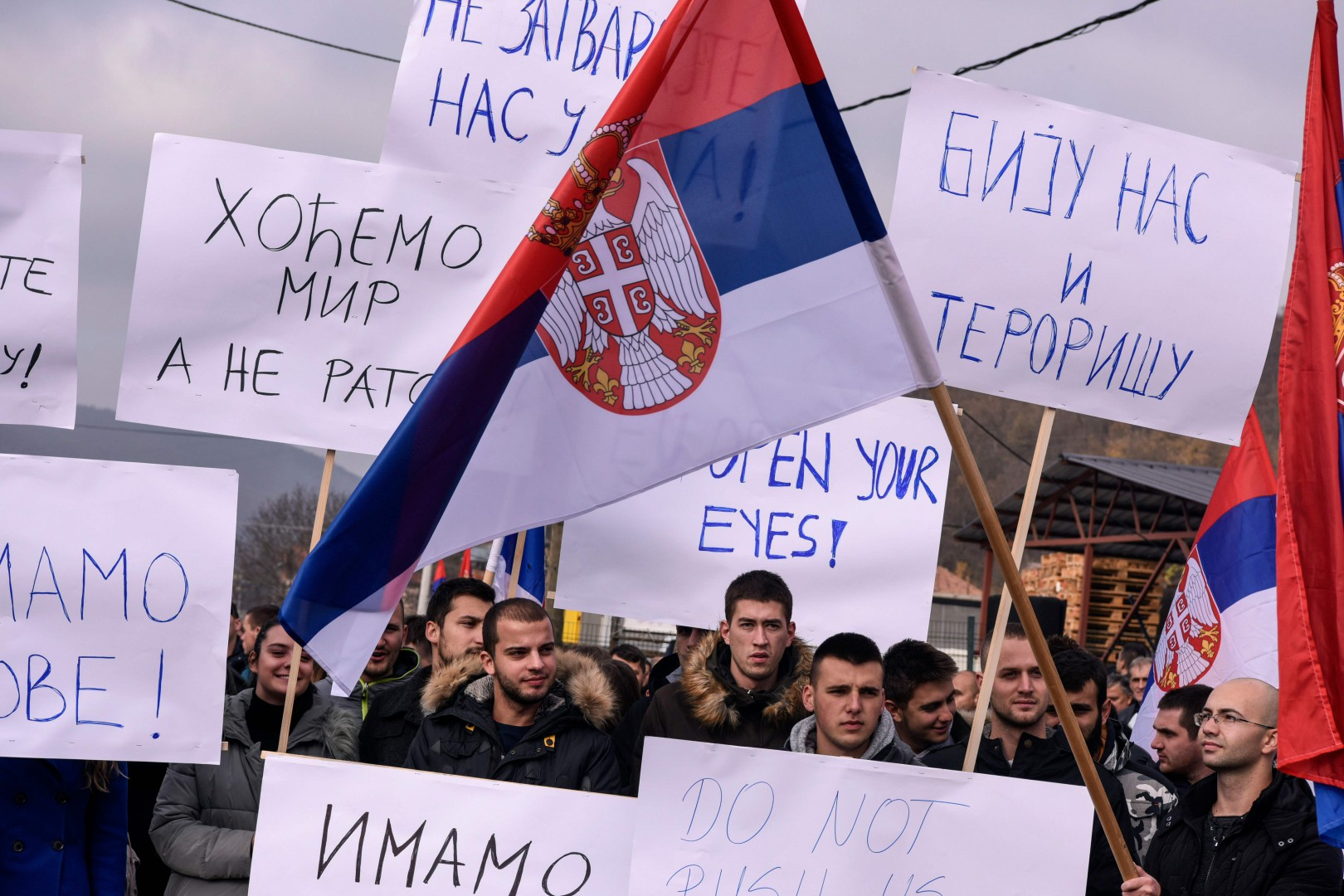 A demonstrator holds the Serbian national flag as Kosovo Serbs gather during a protest in the village of Rudare in northern Mitrovica on November 23, 2018, following Kosovo's move to slap Serbian imports with a 100 percent tariff. - Kosovo's move has triggered a new surge of tensions between the former war foes on November 22. Kosovo announced the tariff on both Serbian and Bosnian goods  -- though excluding international brands -- on November 21 after accusing Belgrade of sabotaging its bid to join Interpol, the international police organisation. Serbia has long fought to thwart Kosovo, which is home to an ethnic Albanian majority, from joining international organisations like the United Nations. (Photo by Armend NIMANI / AFP)