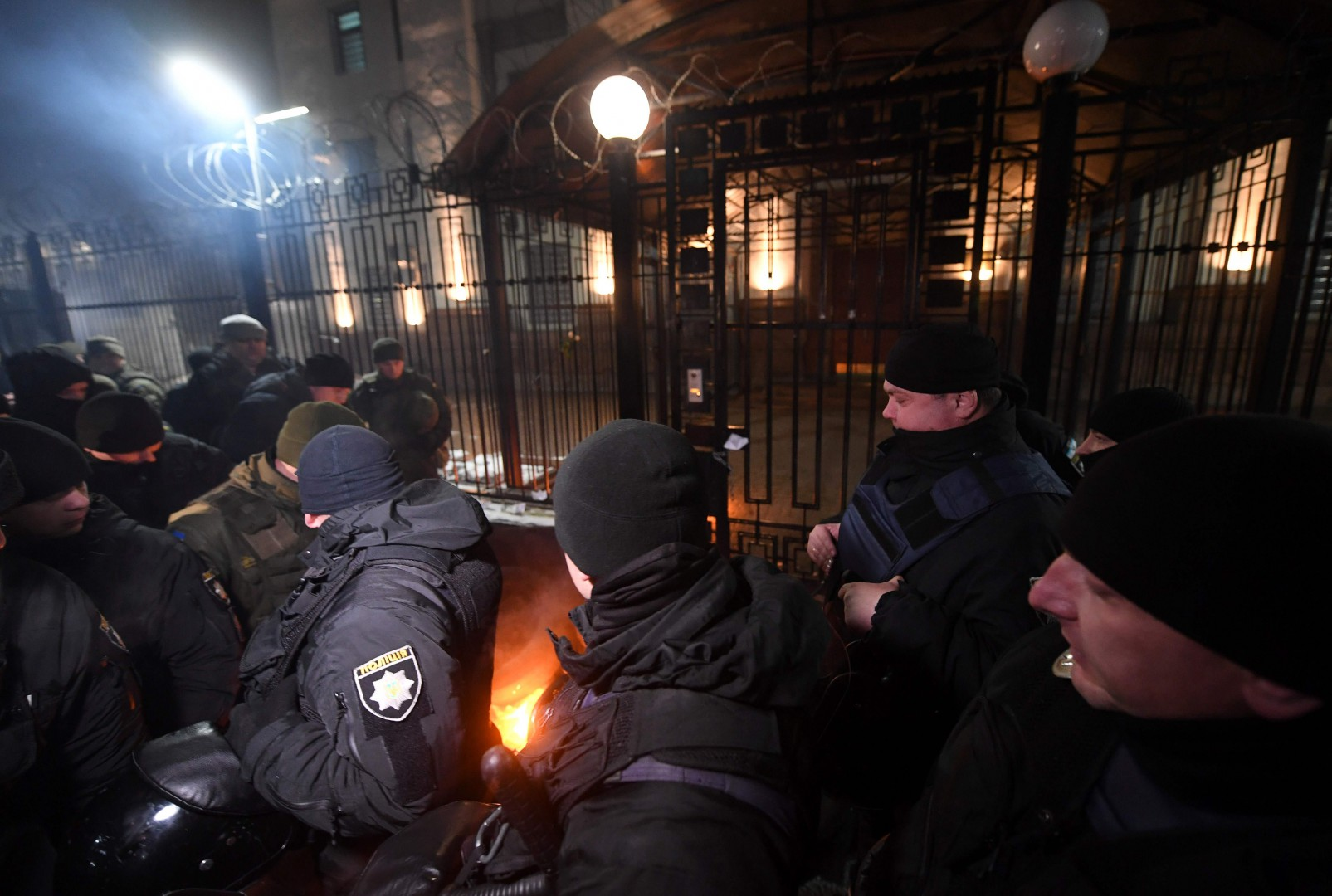 TOPSHOT - Policemen and servicemen of Ukrainian National Guard extinguish a flare thrown by protesters in front of the Russian embassy in Kiev late on November 25, 2018, during a rally following an incident in the Black Sea off Moscow-annexed Crimea, in which three Ukrainian naval vessels were seized by a Russian border guard vessels, as the three ships were on their way through the Kerch Strait heading for the port of Mariupol. - Russia said on November 25 that it has seized three Ukrainian naval ships by force in a strait near Moscow-annexed Crimea, sparking alarm among Kiev's Western allies and raising fears of military escalation. Ukraine's navy had accused Russia of the unprecedented incident including firing on its vessels in the Kerch Strait, a narrow waterway that gives access to the Sea of Azov that is used by Ukraine and Russia. (Photo by Sergei SUPINSKY / AFP)