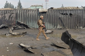 A member of the Afghan security forces walks at the site of a suicide bomb attack outside a British security firm's compound in Kabul, a day after the blast on November 29, 2018. - At least 10 people were killed after a massive blast outside a British security firm's compound in Kabul late November 28, officials said, with the attack claimed by the Taliban in the latest violence to target the Afghan capital. (Photo by NOORULLAH SHIRZADA / AFP)