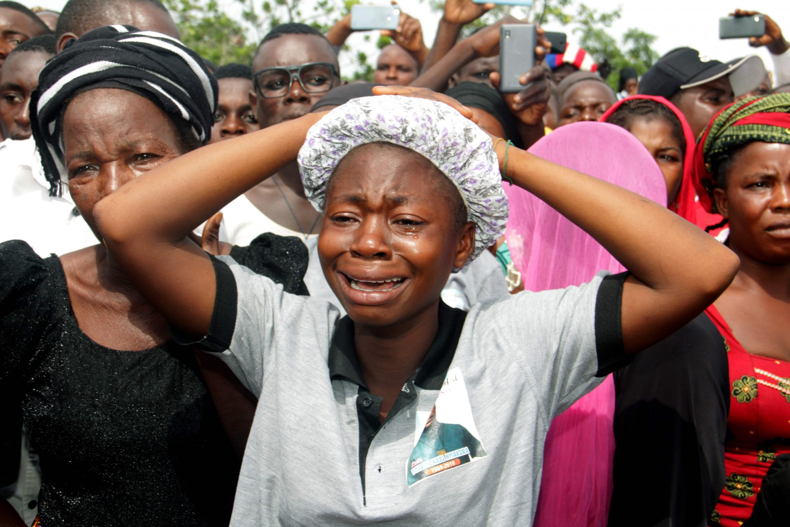 Relatives cry as they mourn during a funeral service for 17 worshippers and two priests, who were allegedly killed by Fulani herdsmen, at Ayati-Ikpayongo in Gwer East district of Benue State, north-central Nigeria on May 22, 2018.  Two Nigerian priests and 17 worshippers have been buried, nearly a month after an attack on their church, as Catholics took to the streets calling for an end to a spiral of violence. White coffins containing the bodies of the clergymen and the members of their congregation were laid to rest in central Benue state, which has been hit by a wave of deadly unrest. / AFP PHOTO / EMMY IBU
