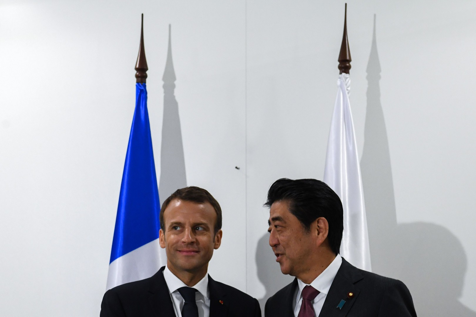 French President Emmanuel Macron (L) meets with Japanese Prime Minister Shinzo Abe on the sidelines of the Saint Petersburg International Economic Forum on May 25, 2018 in Saint Petersburg. / AFP PHOTO / Kirill KUDRYAVTSEV