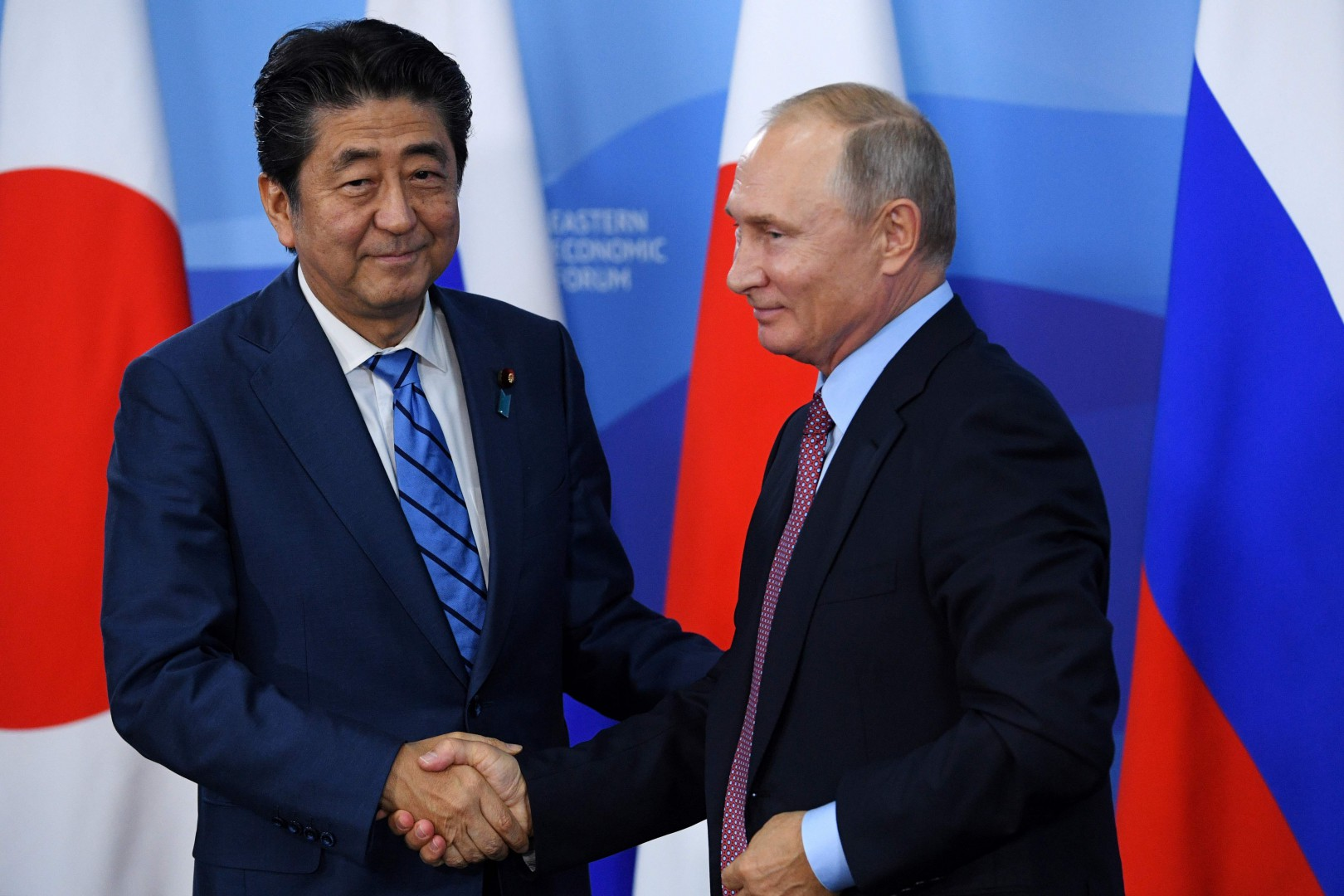 Russian President Vladimir Putin (R) shakes hands with Japanese Prime Minister Shinzo Abe after a press conference following their meeting in Vladivostok on September 10, 2018. (Photo by Kirill KUDRYAVTSEV / AFP)