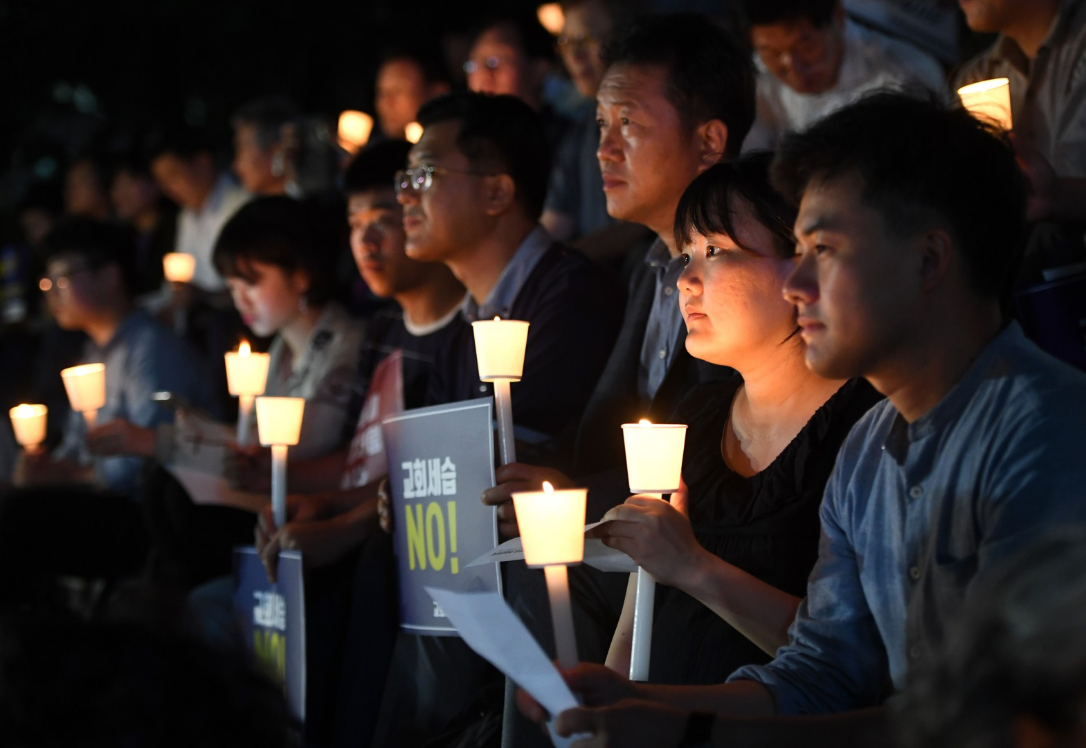 "This picture taken on September 6, 2018 shows protestors holding a candle-lit rally, condemning a controversial father-to-son inheritance of Myungsung Presbyterian Church in Seoul. Placards read ""No to church inheritance!"" - One of the world's largest presbyterian churches has been engulfed by an unholy row after its pastor sought to pass the super-rich South Korean institution into the control of his son. (Photo by Jung Yeon-je / AFP)"