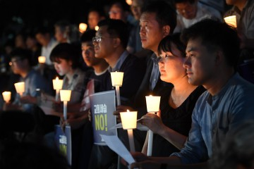 """This picture taken on September 6, 2018 shows protestors holding a candle-lit rally, condemning a controversial father-to-son inheritance of Myungsung Presbyterian Church in Seoul. Placards read """"No to church inheritance!"""" - One of the world's largest presbyterian churches has been engulfed by an unholy row after its pastor sought to pass the super-rich South Korean institution into the control of his son. (Photo by Jung Yeon-je / AFP)"""