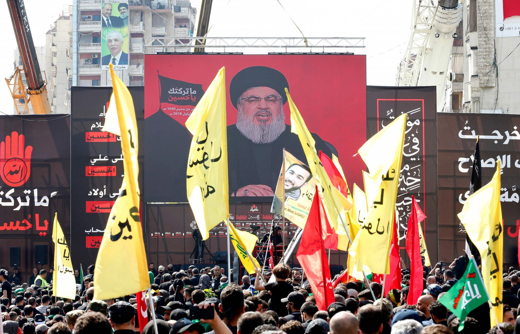 Supporters of Lebanon's Shiite movement Hezbollah gather near a giant poster of their leader Hassan Nasrallah during a ceremony to mark Ashura on September 20, 2018 in Beirut. - Ashura commemorates the death of Imam Hussein, grandson of the Muslim faith's prophet Mohammed, who was killed by the armies of his rival Yazid over the succession for the caliphate near Karbala in 680 AD. (Photo by ANWAR AMRO / AFP)