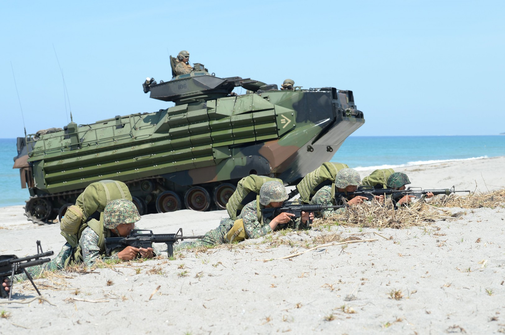Philippine marines take position next to US marines Amphibious Assault Vehicles (AAV) during an amphibious landing exercise at the beach of the Philippine navy training center facing the south China sea in San Antonio town, Zambales province, north of Manila on October 6, 2018. - Japanese troops stormed a South China Sea beach in the Philippines on October 6 in joint military exercises with US and Filipino troops that officials said marked the first time Tokyo's armoured vehicles rolled on foreign soil after World War II. (Photo by TED ALJIBE / AFP)