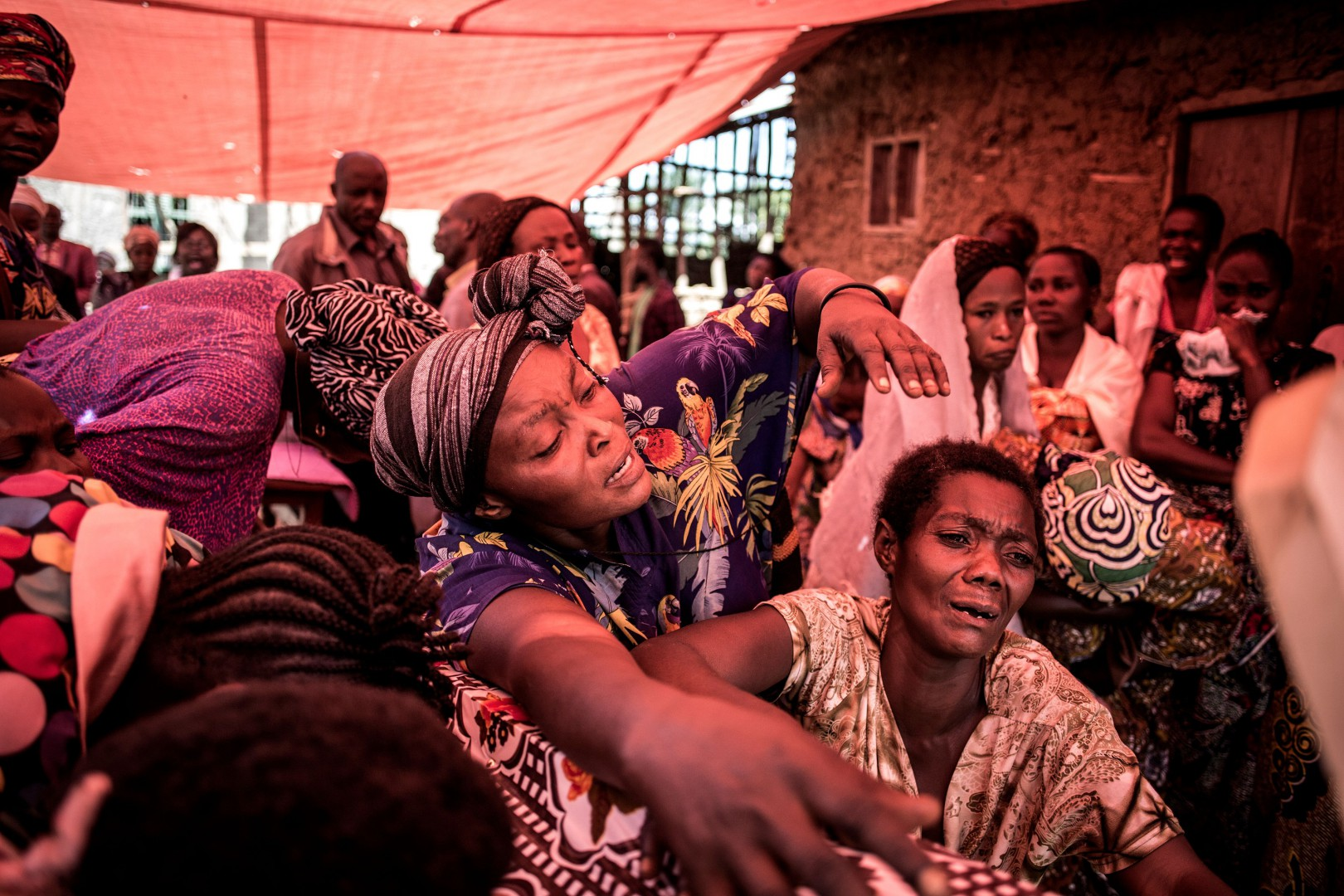 TOPSHOT - Family members of a woman killed in an alleged attack by the Ugandan Allied Democratic Forces(ADF) rebel group react as they see the coffin for the first time on November 12, 2018 in Beni. - Suspected Ugandan rebels killed six people, hacking one woman to death, and kidnapped five others -- mostly children -- in the Democratic Republic of Congo's restive east, officials said on November 11. Officials blamed the two attacks in Beni near the country's border with Uganda on the Ugandan Allied Democratic Forces (ADF), one of several armed movements operating in the region. (Photo by John WESSELS / AFP)