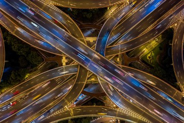 TOPSHOT - This aerial picture taken on the night of November 12, 2018 shows traffic on an elevated intersection in downtown Shanghai. (Photo by Johannes EISELE / AFP)