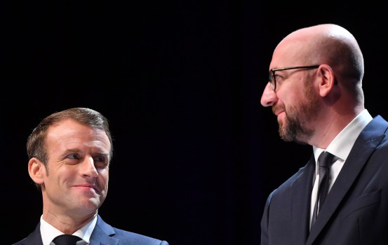 Belgian Prime Minister Charles Michel (R) and French President Emmanuel Macron stand on stage during their visit at the University of Louvain on November 20, 2018, in Louvain-la-Neuve, during a two-day state visit of the French President. (Photo by EMMANUEL DUNAND / AFP)
