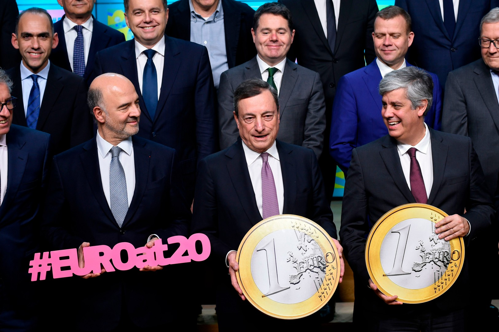 European Commissioner for Economic and Financial Affairs, Taxation and Customs Pierre Moscovici (L) President of the ECB, Mario Draghi, and Portuguese Finance Minister and president of Eurogroup Mario Centeno pose with a replica of an EU coin marking the twentieth anniversary of the Euro during an Eurogroup meeting at the EU headquarters in Brussels on December 3, 2018. (Photo by JOHN THYS / AFP)
